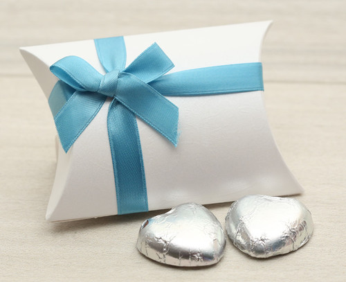 Table Gift in the shape of a Pillow Box  containing two solid milk chocolate hearts and ribboned with a Turquoise satin ribbon.