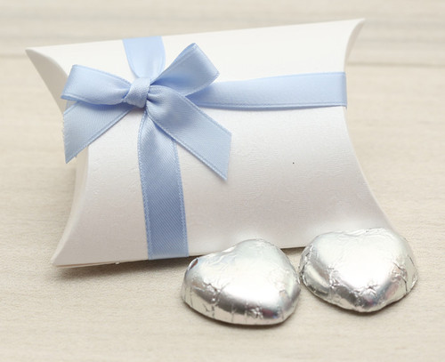 Table Gift in the shape of a Pillow Box  containing two solid milk chocolate hearts and ribboned with a pale blue satin ribbon.