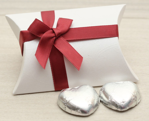 Table Gift in the shape of a Pillow Box  containing two solid milk chocolate hearts and ribboned with a burgundy satin ribbon.
