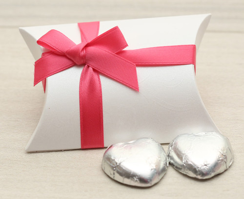 Table Gift in the shape of a Pillow Box  containing two solid milk chocolate hearts and ribboned with a Cerise satin ribbon.