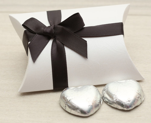 Table Gift in the shape of a Pillow Box  containing two solid milk chocolate hearts and ribboned with a black satin ribbon.