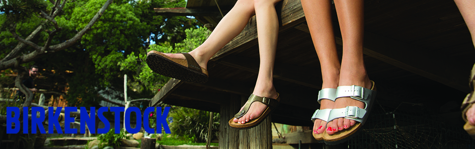 Two people sitting on a dock with their feet hanging off wearing Birkenstock sandals