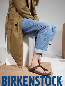 Woman sitting on a wooden box wearing Birkenstock