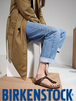 Woman sitting on a wooden box wearing Birkenstock