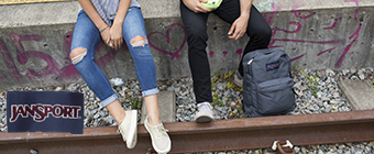 Guy and girl sitting near train track wearing Jansport