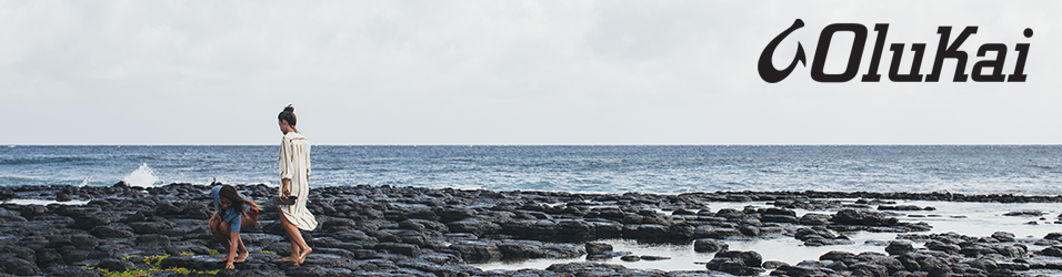 Two women scouring a rocky, scenic seashore in warm weather