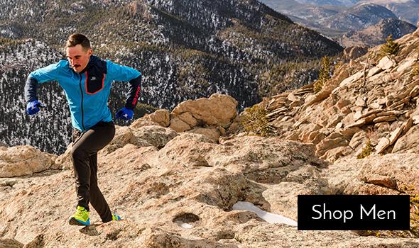 Man hiking up mountains wearing Salomon