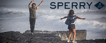 Guy and girl standing on rocks on the beach wearing Sperry