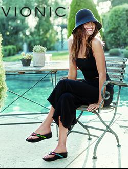 Woman sitting on a chair near a pool wearing Vionic