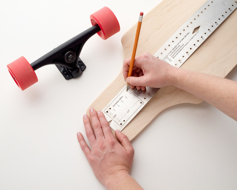 Find your centre line, mark truck hole patterns and distances, draw long straight lines. This ruler bends along the 3-dimensional shapes of your skateboard.
