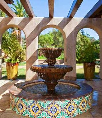handmade cantera stone fountain from Mexico in a garden behind the house