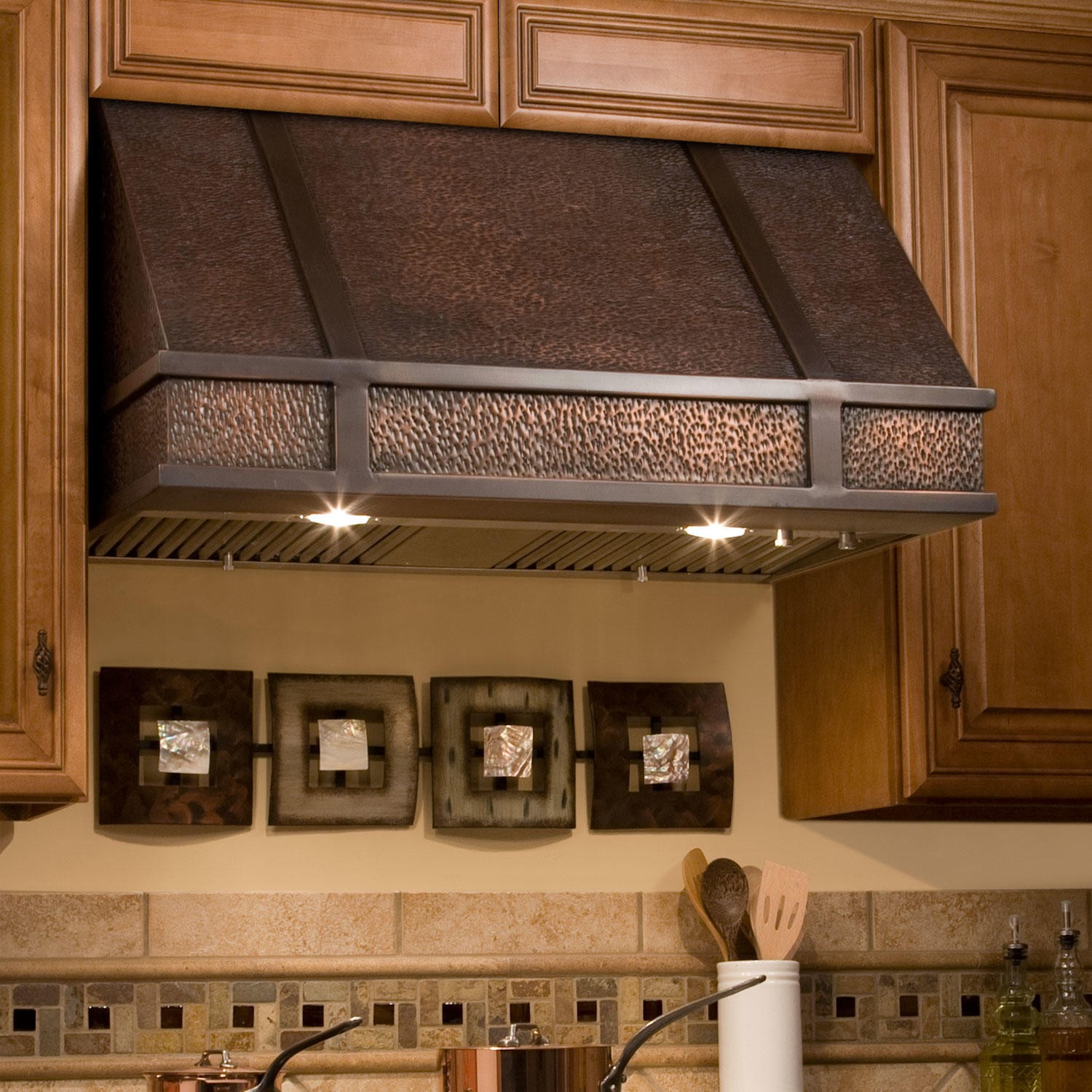 distressed metal copper stove hood installed on a wall of kitchen