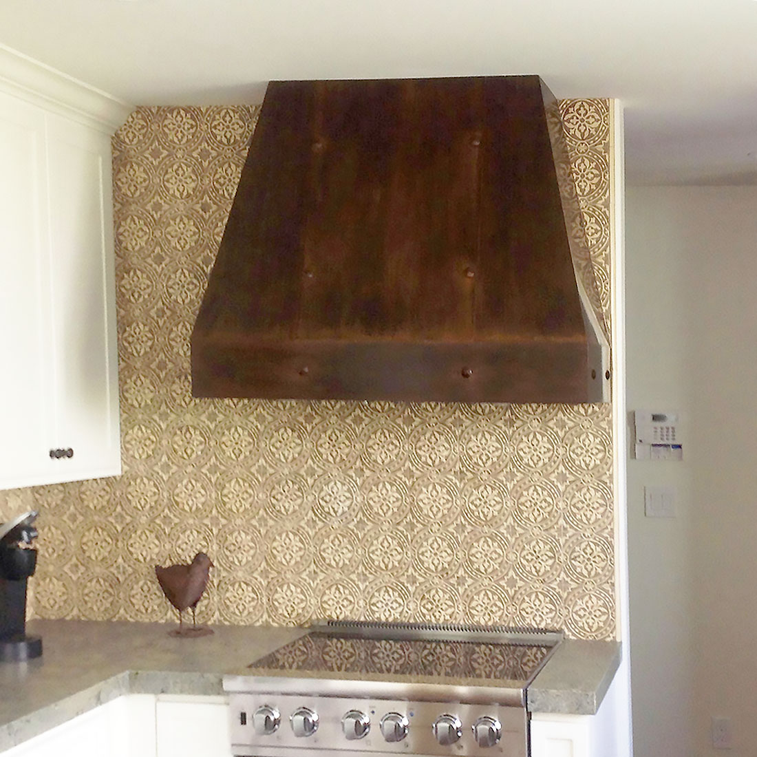 a picture of a small copper range hood on a wall of a kitchen