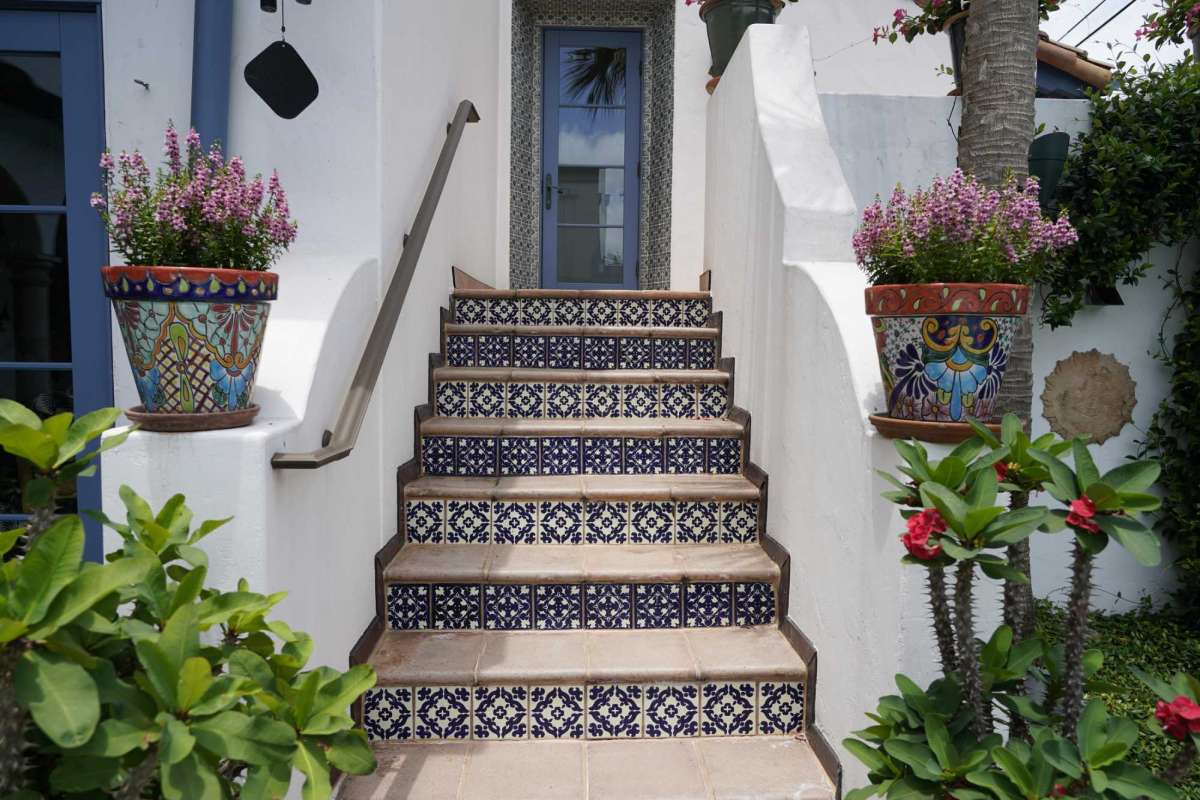 mexican tiles installed on a stair risers outside of the house