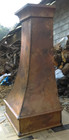 size view of a tall range hood made of hammered copper