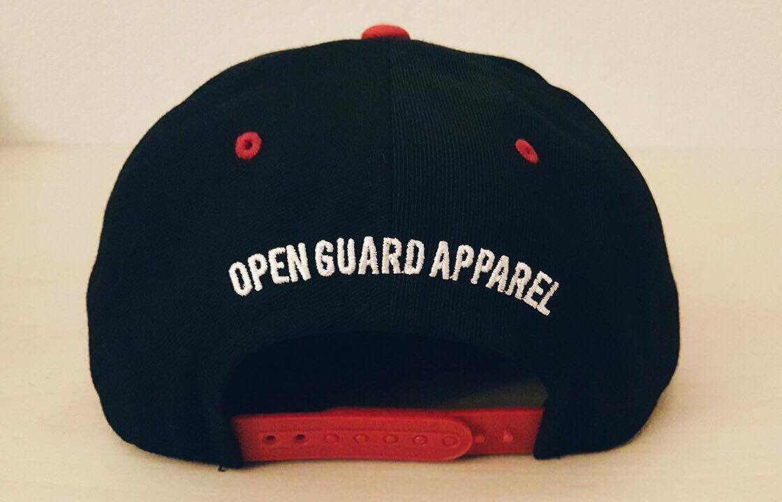 Back of the OGA Open Guard Apparel Jiu Jitsu vs The World Snapback hat.  Red black hat with white embroidery in the background of his picture..  Jiu Jitsu vs the world series from Open guard apparel.   Enjoy Free Shipping on all products storewide today.