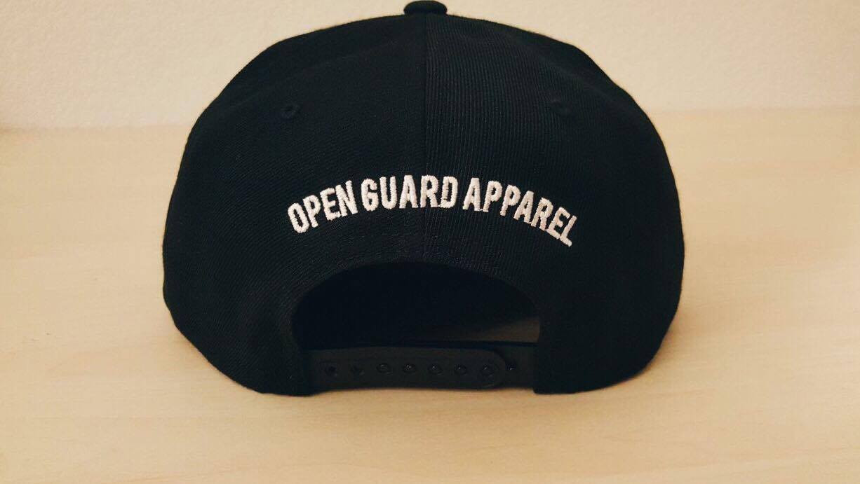 Back of OGA Open Guard Apparel Jiu Jitsu vs The World Snapback hat. Black hat with white embroidery in the background of his picture..  Jiu Jitsu vs the world series from Open guard apparel.   Enjoy Free Shipping on all products storewide today.