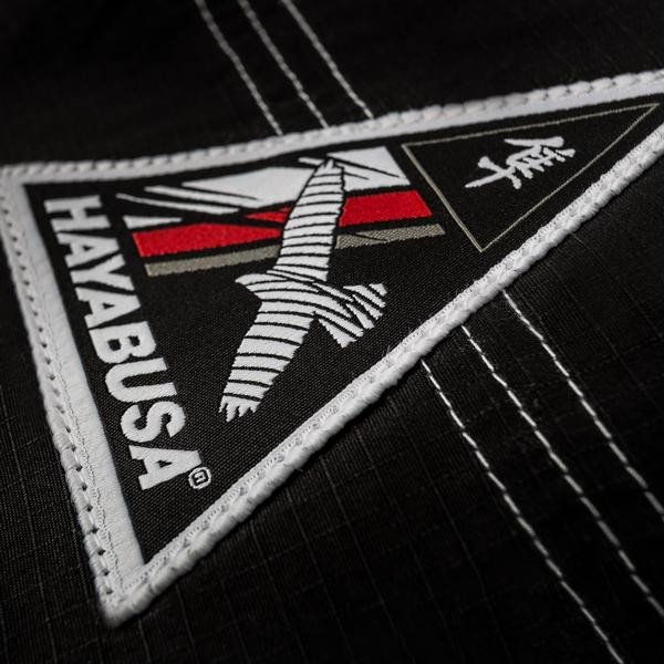 Zoomed into to the triangle woven patch of the Hayabusa Shinju 3 Pearl Weave Jiu Jitsu Gi  in Black Now available at www.thejiujitsushop.com.  The Hayabusa Shinju 3.0 comes in Black blue and white.    Enjoy Free Shipping from The Jiu Jitsu Shop.