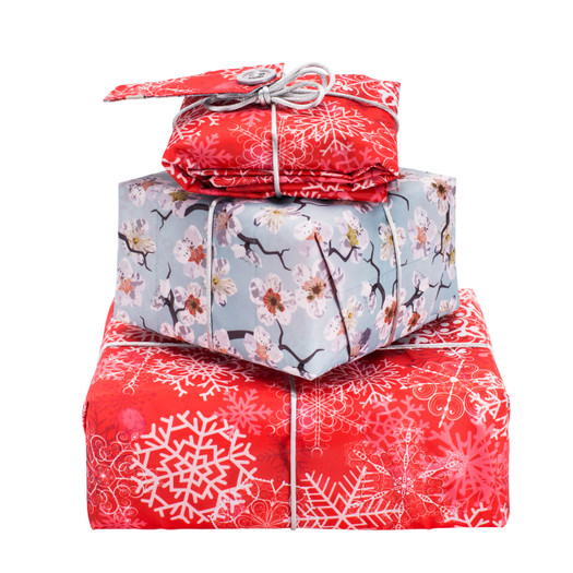 The same size as a standard sheet of wrapping paper, it can be folded to fit a wide variety of different sized gifts.  Pictured here wrapping three different sizes.  Reversible wraps sold individually.