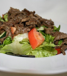 Sizzling marinated Lamb cooked on a vertical spinning grill served over salad tossed with  extra virgin oil and lemon juice.