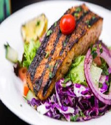 grilled Atlantic wild salmon seasoned  served over house salad and garlic souse