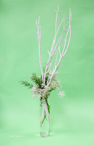 White tall sticks with snowflakes hanging down, a bit of baby's breathe for snow, and a bit of evergreen for this winter wonderland centerpiece.