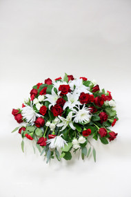 This traditional colored clustered casket spray is a loving tribute. The combination of red and white symbolizes pure love. Roses, carnations, and lilies are classic flowers for a funeral.