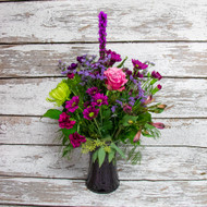 Not sure what to send but know that they love purple? This arrangement is for you! A touch of purple is a special fresh-cut arrangement of mixed seasonal purple flowers in a tall square vase.