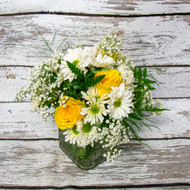 Mixed Flower arrangement in clear vase with yellow accents