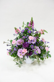 A simple wicker basket filled with soft lavender flowers and greenery.  Small, simple, and thoughtful.
