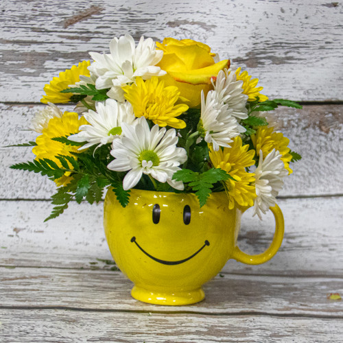 A yellow happy face mug filled with fresh cut white and yellow daisies and green filler.