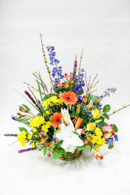 A basket full of sunshine. This is a vibrant combination of bright spring colors and flowers. Perfect item for a celebration of a very special life.