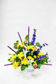 A bold combination of hardy flowers combine red in an urn container. Lilies, daisies, liatris and other flowers come together to make a cheerful tribute.