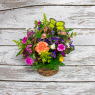A wicker basket filled with bright colored long-lasting flowers like daisies, carnations, alstromeria and dianthus.