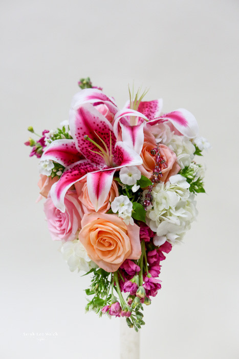 Fun fun fun summer colors with stargazer, peachy roses, white roses and hint of dark pink stock.