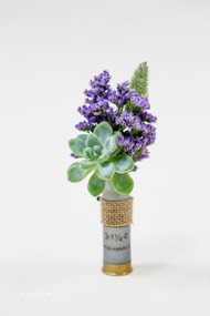 Succulents and purple filler and fun mix in shotgun shell provided by the bride.