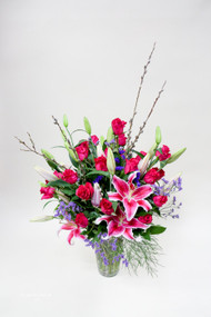 A Beautiful unique fresh flower arrangement designed by the Earle's Girls. great for special occasions like Mother's Day, Make a statement with this variety of Local Grown Lilies, fun blooming branches,  and gorgeous premium roses mix from you Loveland Florist!