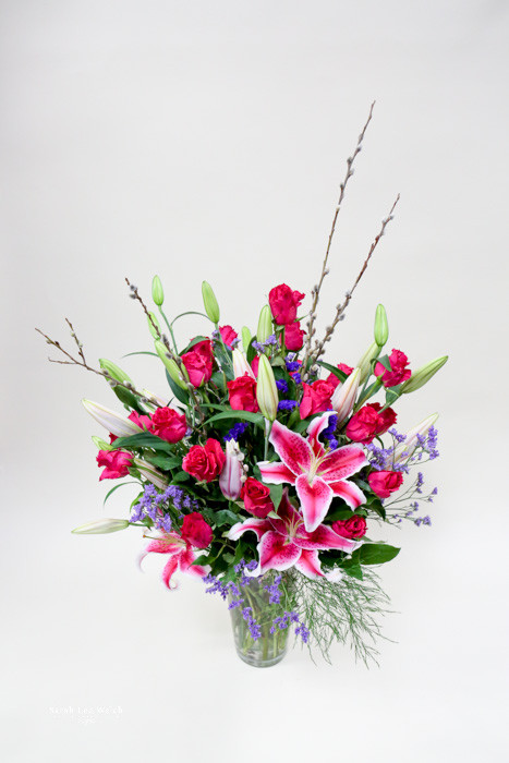 A Beautiful unique fresh flower arrangement designed by the Earle's Girls.Perfect for special occasions!  Make a statement with this variety of Local Grown Lilies, fun blooming branches,  and gorgeous premium rose mix from you Loveland Florist!