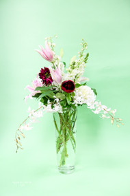 A tall  vase is just the answer to show off pink lilies, long white orchids, fabulous burgundy dahlias and cascading greens.