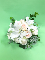 Great things come in small packages, with white lilies, blush garden roses and dusty miller in these smaller bridal bouquet.