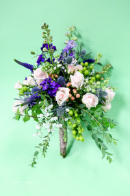 Tons of movement and texture define this handtied bouquet.  Lots of wild grasses, eucalyptus, larkspur, delphinium, hypericum berries, blush roses and veronica make this a fun summer look.