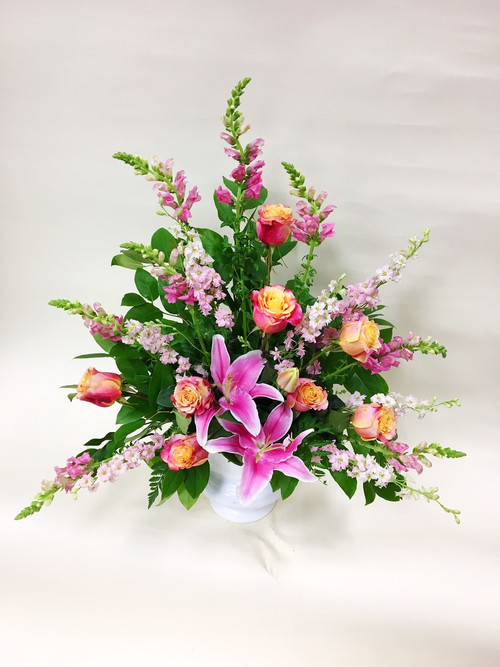 A Bright, Mixed, One Sided sympathy tribute, designed with bright pinks and peach colors. Designed with two tone premium roses and local grown Lilies.