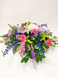 Beautiful fresh flower casket spray designed with pinks, purples, and whites. Designed locally at Earle's Loveland with a variety of fresh flowers.