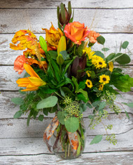This beautiful arrangement in a clear vase, with fall ribbon and fall colored lilies and roses and a perfect touch to your autumn decorations.