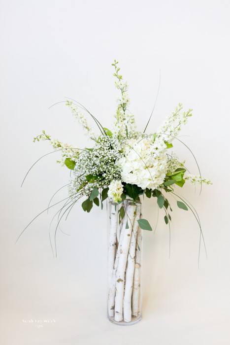 Here's a show stopping centerpiece in birch log filled cylinders with white hydrangea, larkspur, bear grass and eucalyptus.