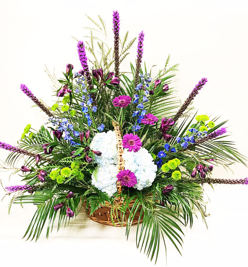 A Mix of purples pinks and peaceful whites arranged in a one sided basket tribute
