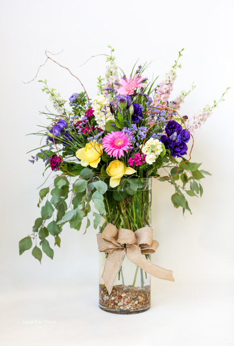 Premium mixed fresh cut flower arrangement with premium long stemmed roses and other mixed flowers arranged in an upgraded glass vase with burlap accent and colored fillers.