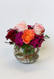 Mixed fresh cut premium roses arranged in a glass bowl.