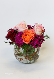 Mixed fresh cut premium roses arranged in a glass bowl.