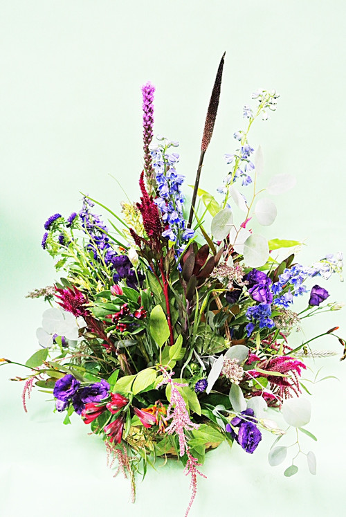 Beautiful mix of fresh flowers arranged in an all around basket wedding decor